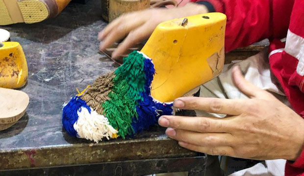 Un grupo de artesanos marroquíes confeccionan las babuchas boucharoite a mano